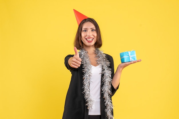 Świąteczny nastrój z pozytywną biznesową damą w garniturze z czapką świąteczną i prezentem, robiąc ok gest na żółto