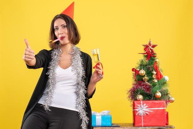 Świąteczny nastrój z pozytywną piękną damą trzymającą czerwony kubek i wykonującą ok gest w biurze na żółto