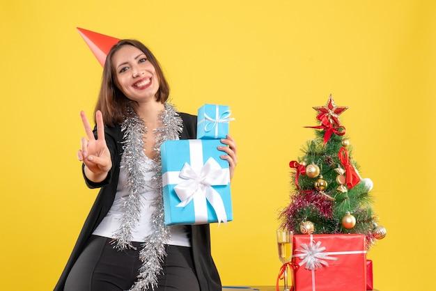 Świąteczny nastrój z pozytywną piękną damą w kapeluszu xsmas, trzymając prezenty z gestem zwycięstwa w biurze na żółto