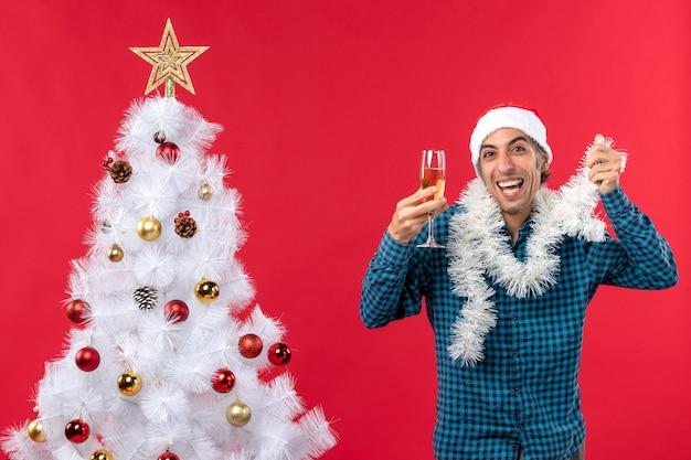 Świąteczny nastrój z szalonym emocjonalnym młodzieńcem w kapeluszu świętego mikołaja i podnoszącym kieliszek wina wiwatuje w pobliżu choinki
