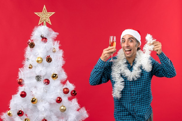 Świąteczny nastrój z szalonym młodym mężczyzną w czapce świętego mikołaja i podnoszącym kieliszek wina wiwatuje w pobliżu choinki