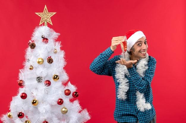 Świąteczny nastrój z szczęśliwym młodym człowiekiem z czapką świętego mikołaja w niebieskiej koszuli z paskiem, podnosząc kieliszek wina w pobliżu choinki