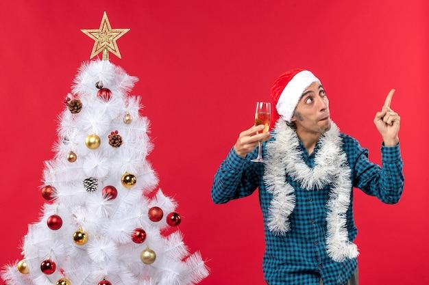 Świąteczny nastrój z szczęśliwym młodym mężczyzną w czapce świętego mikołaja w niebieskiej koszuli w paski, podnoszącym kieliszek wina, pokazujący powyższe w pobliżu choinki
