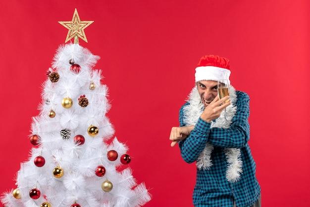Świąteczny nastrój z szczęśliwym szalonym młodym człowiekiem z czapką świętego mikołaja w niebieskiej koszuli w paski, podnosząc kieliszek wina w pobliżu choinki