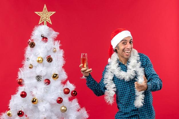Świąteczny nastrój z uśmiechem młodzieńca w kapeluszu świętego mikołaja w niebieskiej koszuli z paskiem, trzymając kieliszek wina w pobliżu choinki