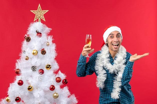 Świąteczny nastrój z uśmiechem szczęśliwego młodego człowieka z czapką świętego mikołaja w niebieskiej koszuli z paskiem, trzymając kieliszek wina w pobliżu choinki