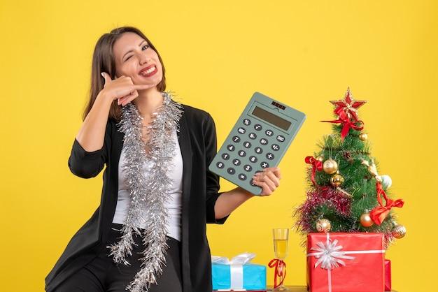 Świąteczny nastrój z uśmiechniętą piękną kobietą stojącą w biurze i wskazującym kalkulatorem wykonującym wezwanie do mnie gestem w biurze na żółto