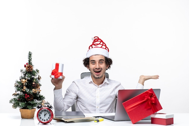 Świąteczny nastrój z uśmiechniętym młodym biznesmenem w kapeluszu świętego mikołaja i szczęśliwie trzymając jego prezent na białym tle