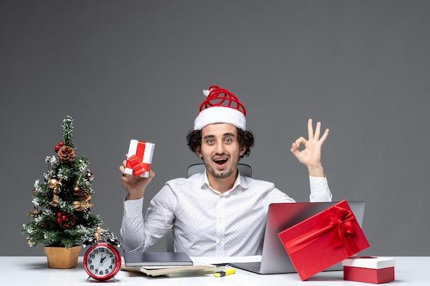 Świąteczny nastrój z uśmiechniętym młodym biznesmenem w kapeluszu świętego mikołaja i trzymając jego prezent, robiąc gest okularów na ciemnym tle