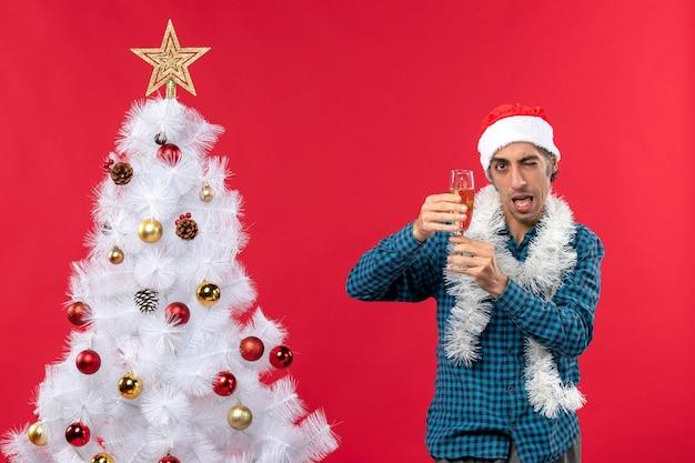 Świąteczny nastrój z zabawnym młodzieńcem w kapeluszu świętego mikołaja w niebieskiej koszuli w paski, podnosząc kieliszek wina w pobliżu choinki