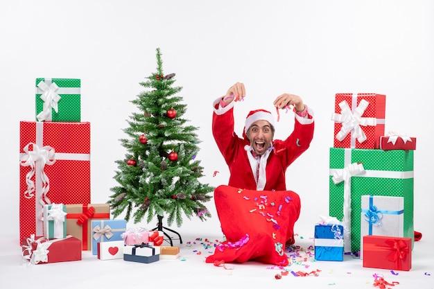 Świąteczny nastrój z zabawnym pozytywnym szczęśliwym świętym mikołajem siedzącym na ziemi i bawiącym się dekoracjami świątecznymi w pobliżu prezentów i dekorowanego drzewa xsmas na białym tle