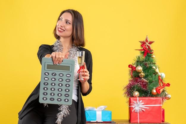 Świąteczny nastrój z zadowoloną piękną panią stojącą w biurze i trzymającą kalkulator podnoszący wino w biurze na żółto