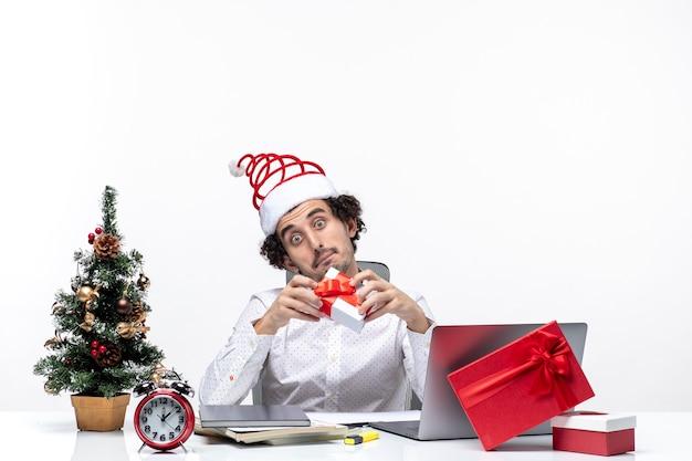 Świąteczny nastrój z zaskoczonym biznesmenem w kapeluszu świętego mikołaja podnoszącym prezent i patrząc na niego na białym tle