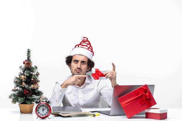Świąteczny nastrój z zaskoczonym niezadowolonym biznesmenem z czapką świętego mikołaja, wskazując prezent na białym tle