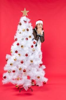 Świąteczny nastrój z zszokowaną młodą piękną damą w czarnej sukience z czapką mikołaja
