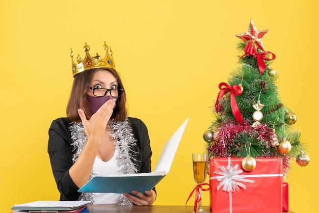 Świąteczny nastrój z zszokowaną piękną damą w garniturze w koronie z maską medyczną trzymającą dokumenty w biurze