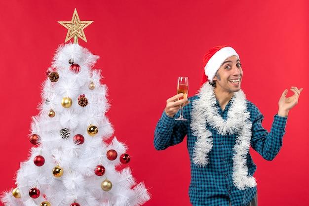 Świąteczny nastrój ze szczęśliwym młodym mężczyzną w czapce świętego mikołaja w niebieskiej koszuli w paski podnoszący kieliszek wina pokazujący lewą stronę w pobliżu choinki