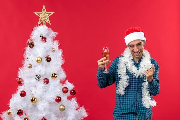 Świąteczny nastrój ze szczęśliwym szalonym emocjonalnym ciekawym młodzieńcem w czapce świętego mikołaja w niebieskiej koszuli w paski, podnosząc kieliszek wina w pobliżu choinki