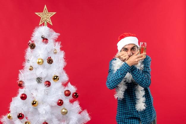 Świąteczny nastrój ze szczęśliwym szalonym emocjonalnym młodym człowiekiem z czapką świętego mikołaja w niebieskiej koszuli w paski, podnosząc kieliszek wina w pobliżu choinki