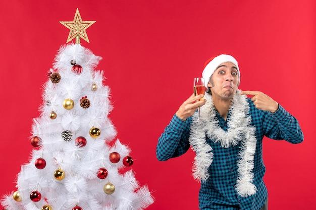 Świąteczny nastrój ze szczęśliwym szalonym emocjonalnym młodym mężczyzną w czapce świętego mikołaja w niebieskiej koszuli w paski podnoszący kieliszek wina, wskazujący na choinkę