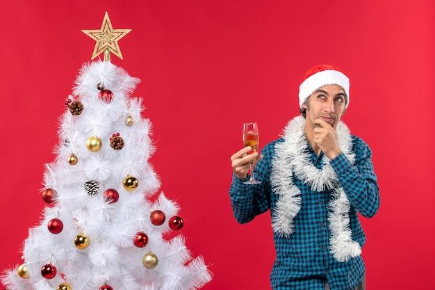 Świąteczny nastrój ze szczęśliwym szalonym emocjonalnym zdezorientowanym młodym mężczyzną z czapką świętego mikołaja w niebieskiej koszuli w paski, podnoszącym kieliszek wina w pobliżu choinki