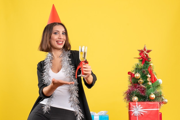 Świąteczny nastrój ze zdezorientowaną piękną damą trzymającą wino i mówiącą o czymś w biurze na żółto