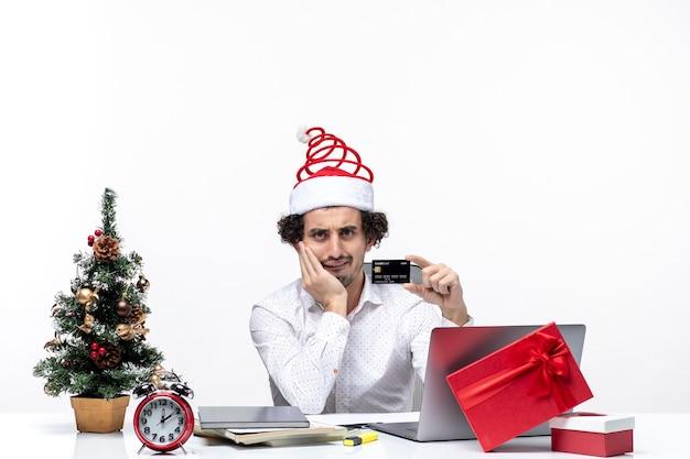 Świąteczny nastrój ze zdezorientowanym biznesmenem z czapką świętego mikołaja trzymającego kartę bankową i wkładającego rękę pod brodę w biurze