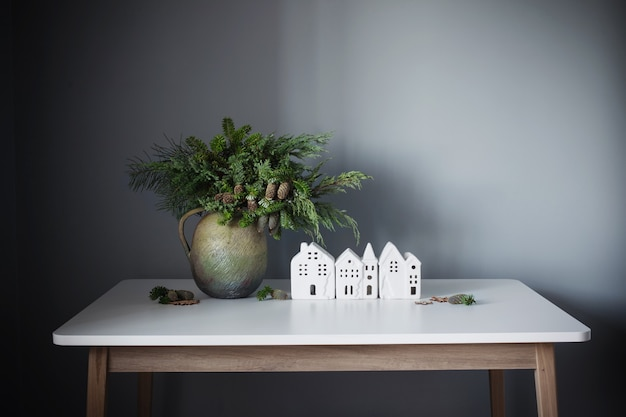 Świąteczny naturalny bukiet w starym ceramicznym dzbanku z białymi domami na szarej ścianie w tle