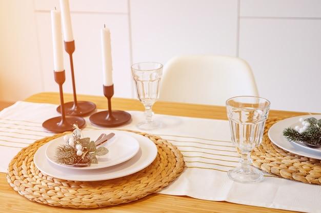 Świąteczny obiad przy świecach, nakrycie stołu w nowoczesnej kuchni.