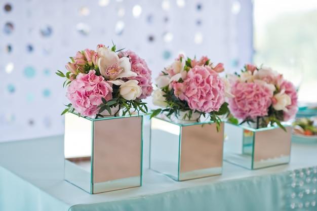 Świąteczny obiad weselny, stół pary młodej udekorowany kwiatami.