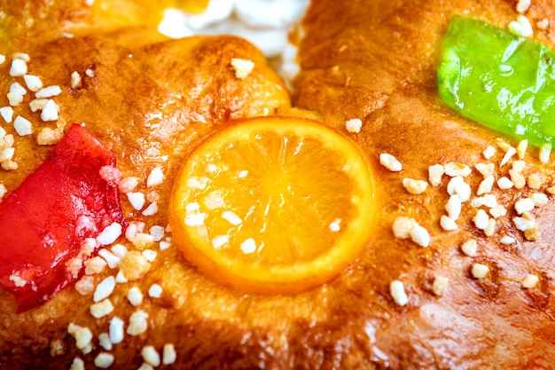 Świąteczny okrągły tort owocowy ozdobiony gałązką jodły, glazurowanymi owocami i orzechami na drewnianym stole.