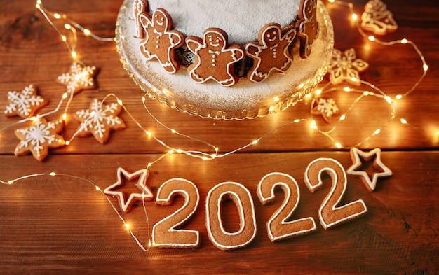 Świąteczny placek ozdobiony ciasteczkami postacie ludzi na stole z numerami nowego roku