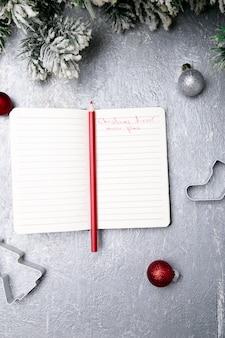 Świąteczny plan menu. tło do pisania menu bożego narodzenia. widok z góry. notatnik na szarym tle z dekoracją.