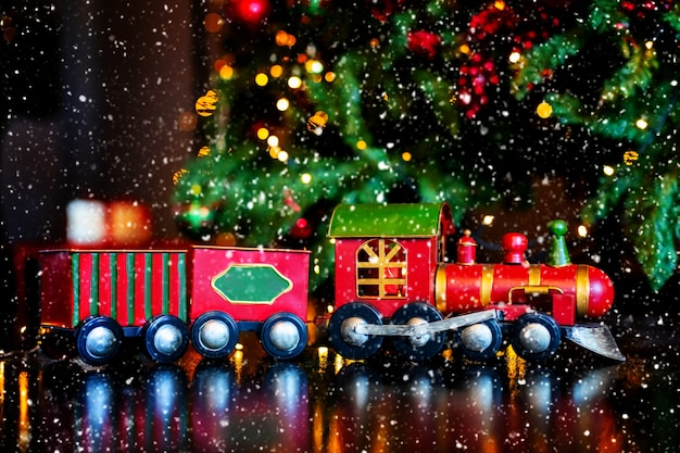 Świąteczny pociąg z zabawkami przy eleganckiej, niewyraźnej choince i światłach