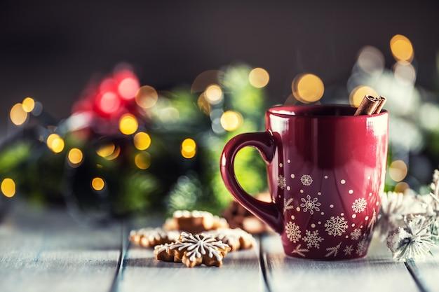Świąteczny poncz w czerwonej filiżance z piernikowymi cynamonami i świątecznymi dekoracjami.