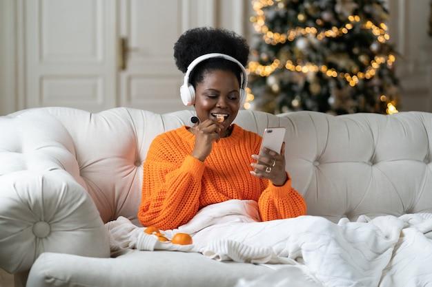 Świąteczny poranek w domu czarna dziewczyna odpoczywa po imprezie sylwestrowej w łóżku przewiń zdjęcia w mediach społecznościowych