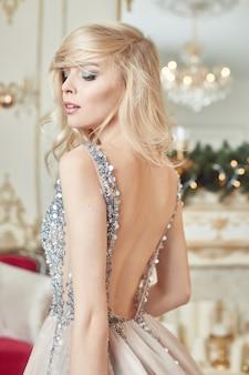 Świąteczny portret kobiety w błyszczącej świątecznej sukni na świąteczny wystrój w eleganckim wnętrzu. kobieta przygotowuje się do świętowania bożego narodzenia i nowego roku