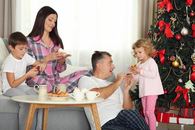 Świąteczny portret rodzinny przy śniadaniu w salonie w domu wakacyjnym, rano