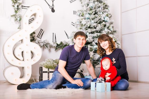 Świąteczny portret rodziny w domu holiday living room, dekorowanie domu przez xmas tree