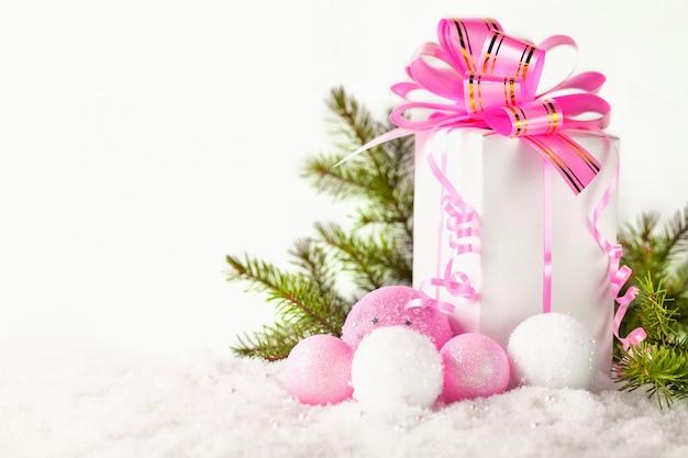 Świąteczny prezent i różowa piłka na śniegu