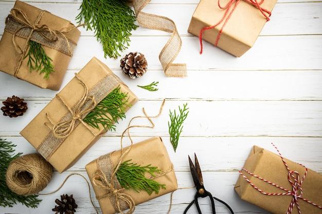 Świąteczny prezent lub pudełko prezentowe owinięte papierem kraft z dekoracją na rustykalnym drewnianym tle