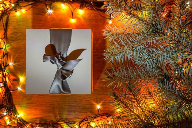 Świąteczny prezent na drewnianym tle z girlandą i świerkowymi gałązkami.