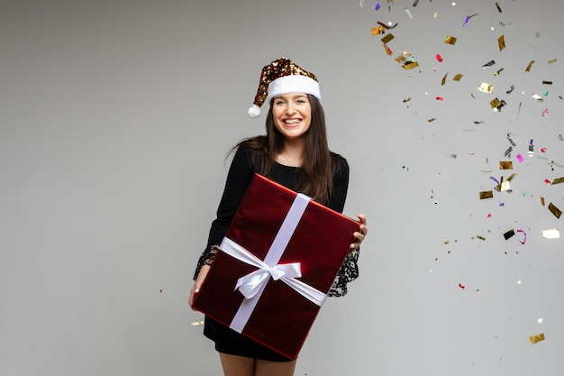 Świąteczny prezent na nowy rok w rękach kobiet, szczęśliwa dziewczyna w czapce mikołaja z okazji ferii zimowych