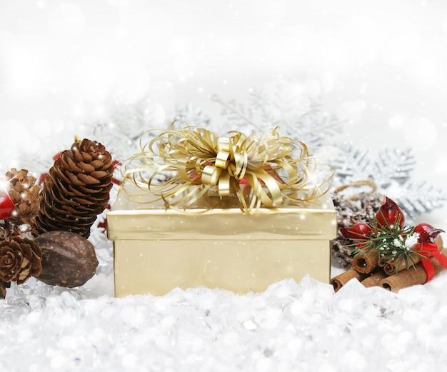 Świąteczny prezent położony w śniegu z szyszek sosnowych i cynamonu