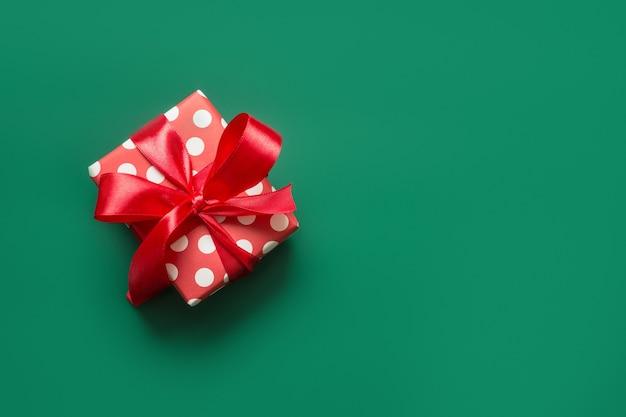 Świąteczny prezent w czerwono-białym opakowaniu w kropki i czerwoną kokardkę na zielonym polu