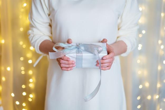 Świąteczny prezent w ludzkich rękach świąteczna tapeta plakat konceptualny obraz z białą ścianą tła...