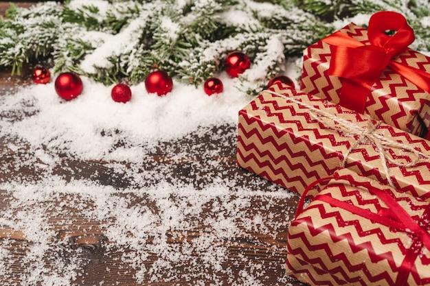 Świąteczny prezent z kokardą z bliska na podłoże drewniane ze śniegiem