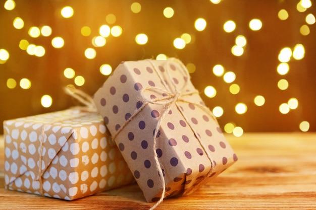 Świąteczny prezenta pudełko na drewnianym stole przeciw brown bokeh tłu