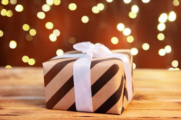 Świąteczny prezenta pudełko na drewnianym stole przeciw brown bokeh