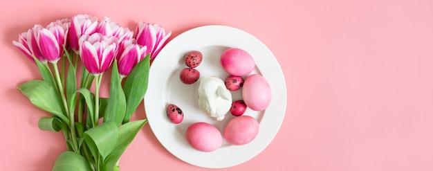 Świąteczny różowy stół wielkanocny z jajkami, królikiem i bukietem tulipanów. transparent. skopiuj miejsce, widok z góry, płaski układ.